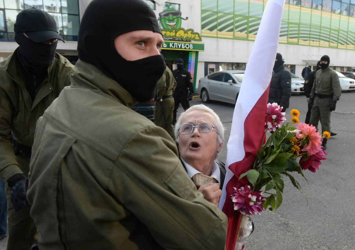 Naamioitunut mies pitää kiinni vanhaa naista, jolla on kukkakimppu kädessään.