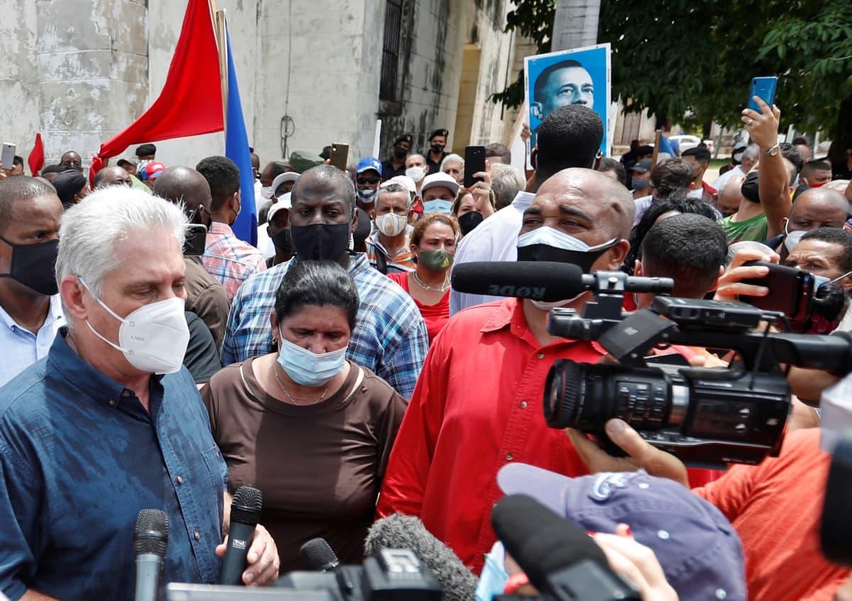 Harmaatukkainen mies maski kasvoillaan puhuu kameroiden ja mikrofonien edessä väkijoukon keskellä.