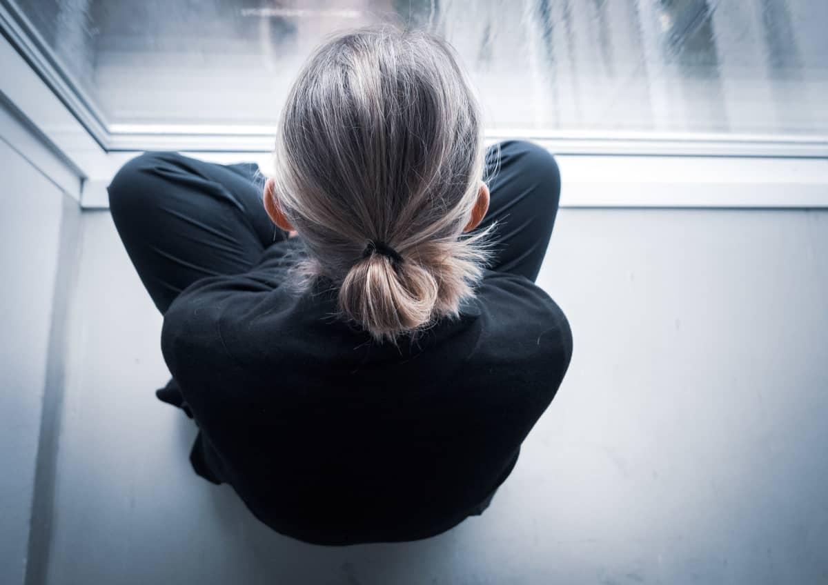 nainen istuu lattialla ja katselee kerrostalon ikkunasta alas.