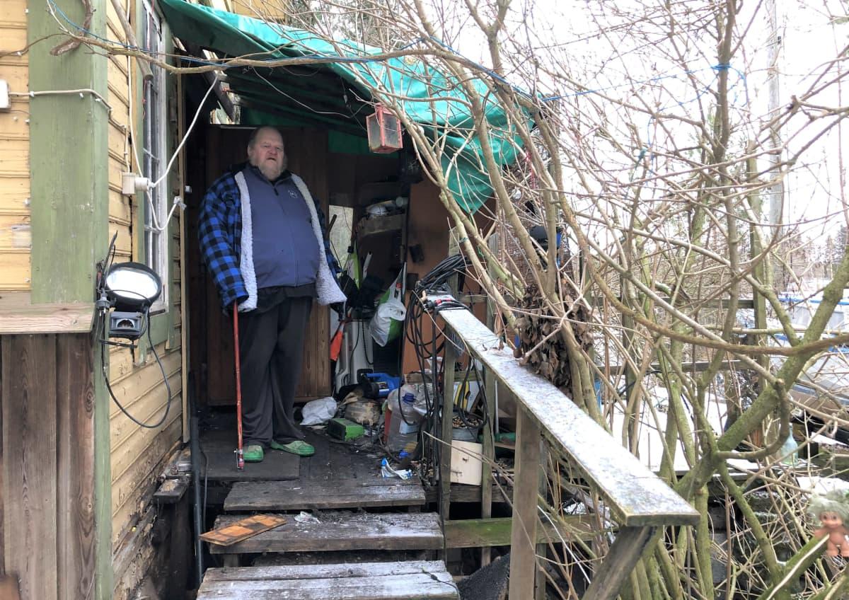 mies seisoo talonsa kuistilla