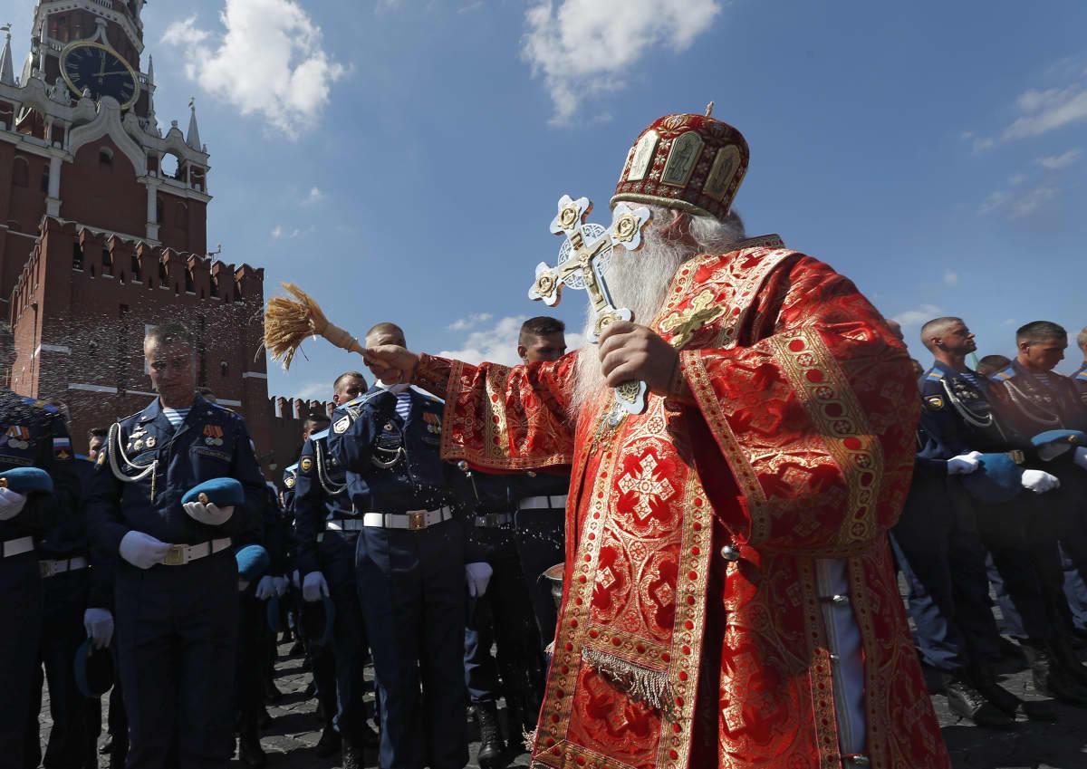Ortodoksipappi pirskottaa vettä sotilaiden päälle.