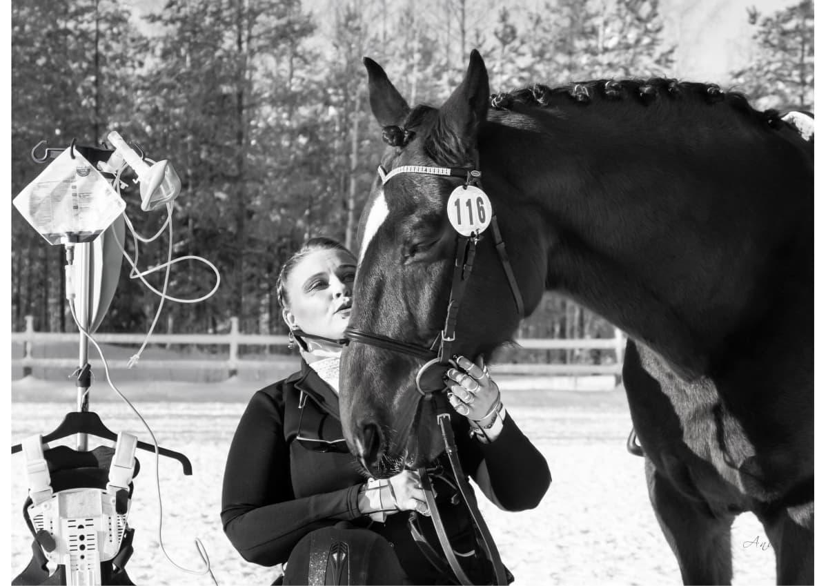 Taru Turkulainen poseeraa hevosensa kanssa