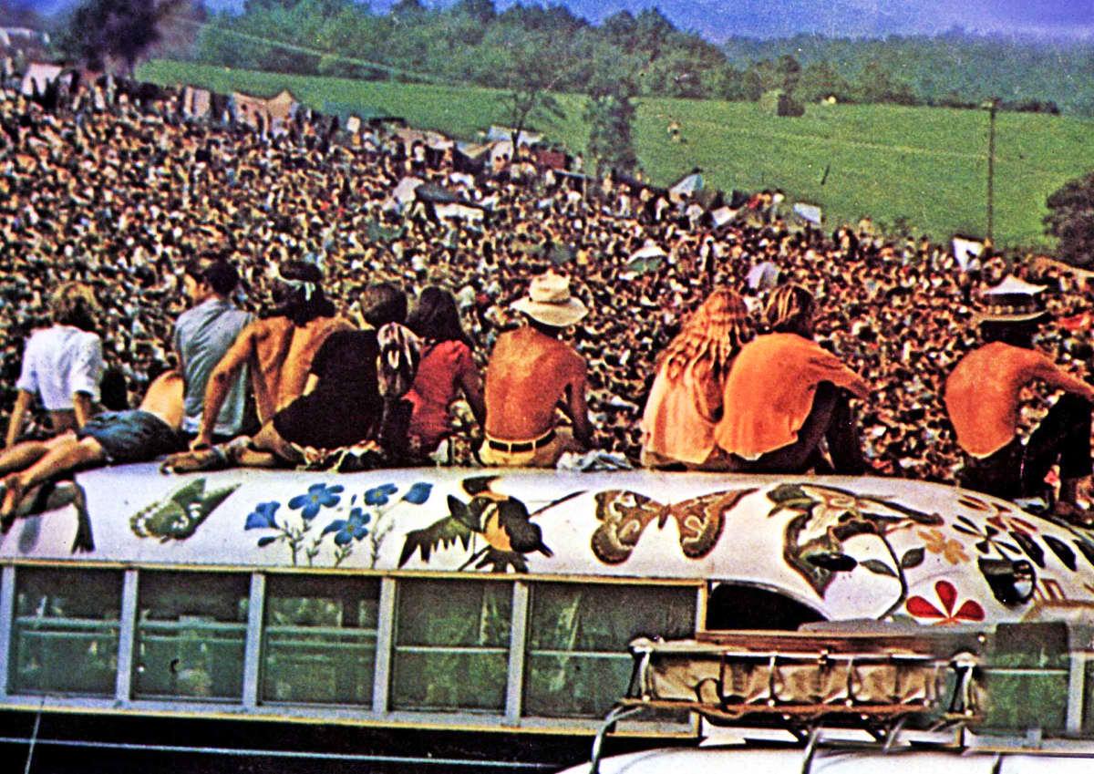 Yleisöä vuoden 1969 Woodstockin rockfestivaaleilla. Edessä olevat ihmiset istuvat bussin katolla.