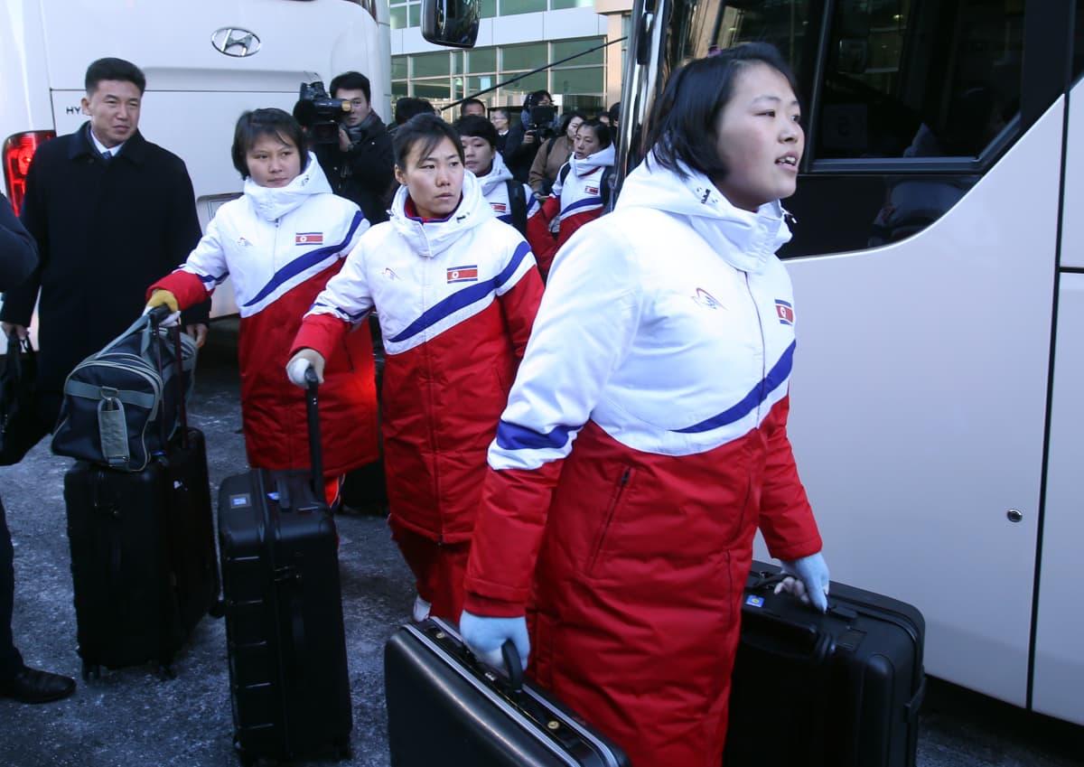 Pohjoiskorealaisia naisjääkiekkoilijoita tulossa bussista.