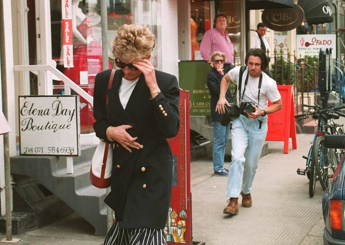 Miesvalokuvaaja jahtaa Dianaa kadulla.