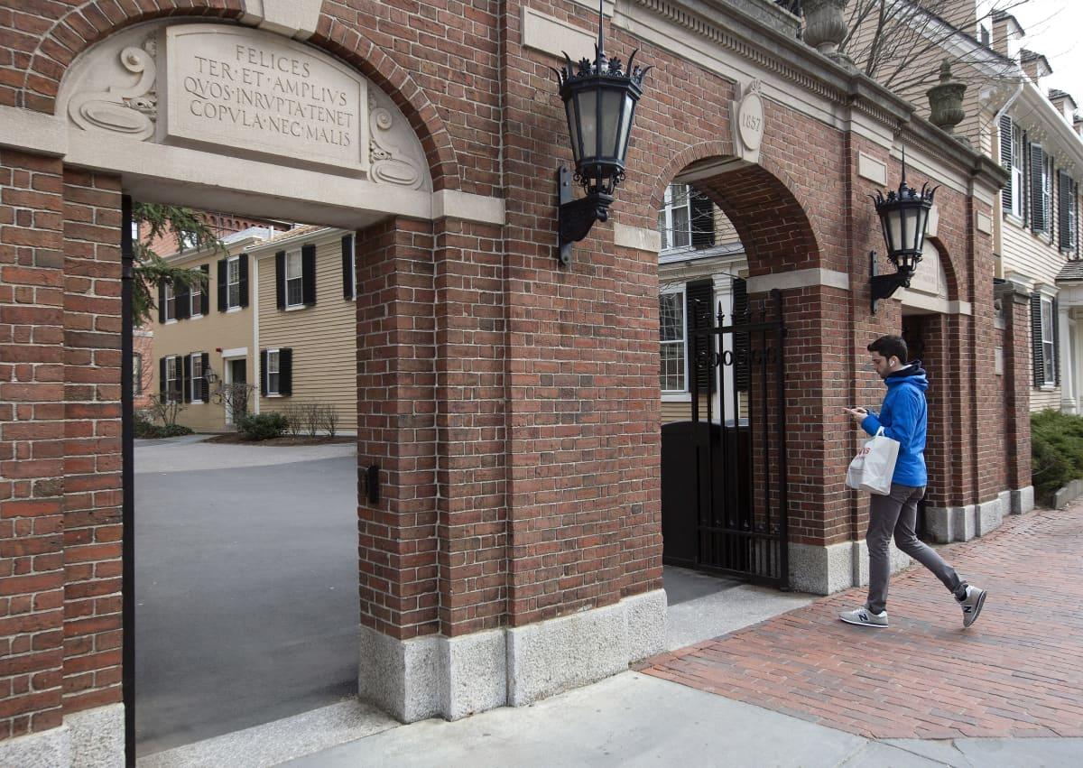 Nuori mies kävelee sisään Harvardin yliopiston porteista.