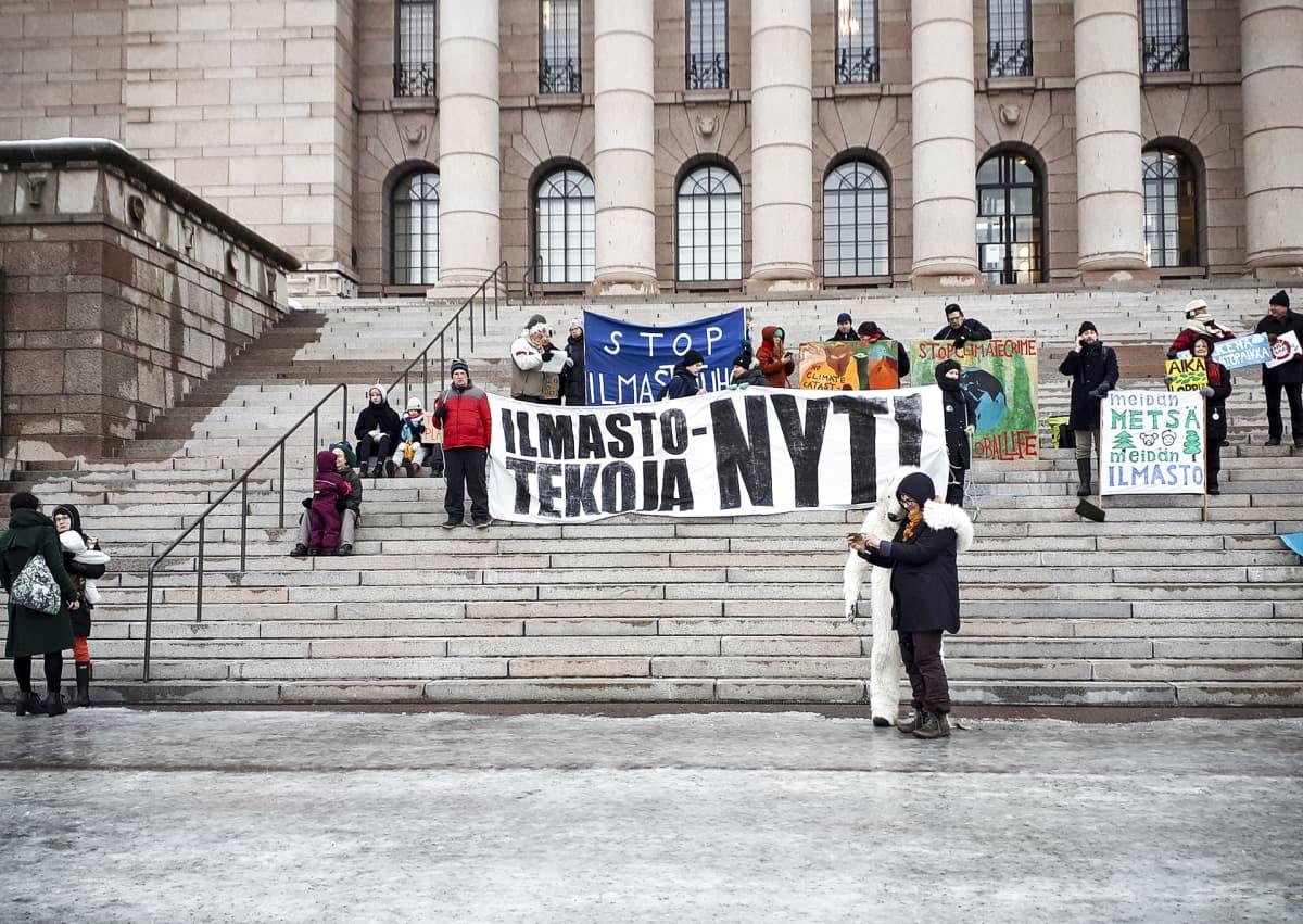 Mielenosoittajia Eduskuntatalon portailla perjantaiaamuna 8. helmikuuta.