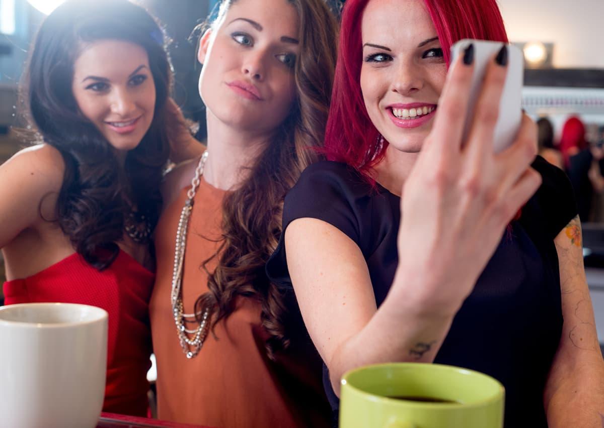 Kolme nuorta naista ottaa puhelimella kuvaa itsestään.