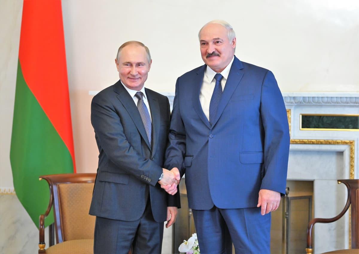 Putin kättelee Lukašenkaa ja hymyilee kameralle. Myös Lukašenka hymyilee. Miehet poseeraavat kameroilla timmissa puvuissa. Taustalla huoneessa näkyy Valko-Venäjän lippu.