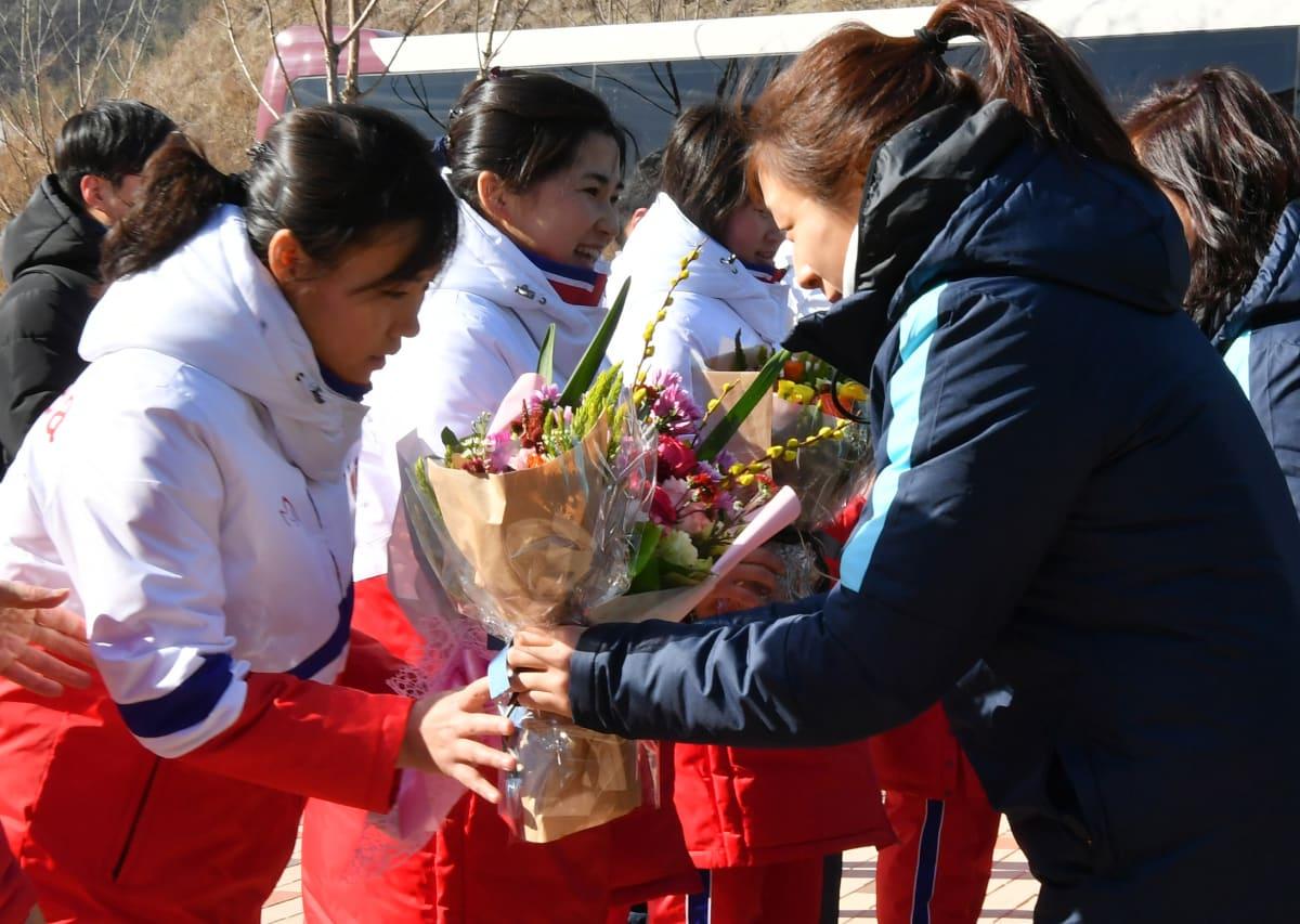 Pohjoiskorealaiset jääkiekkoilijat saivat tervetulokukat eteläkorealaisilta joukkuetovereiltaan.