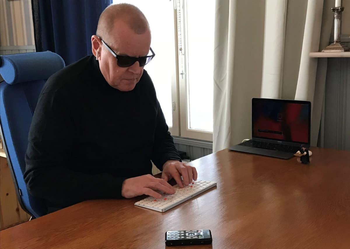 Keijo Raitanen työpöytänsä ääressä.