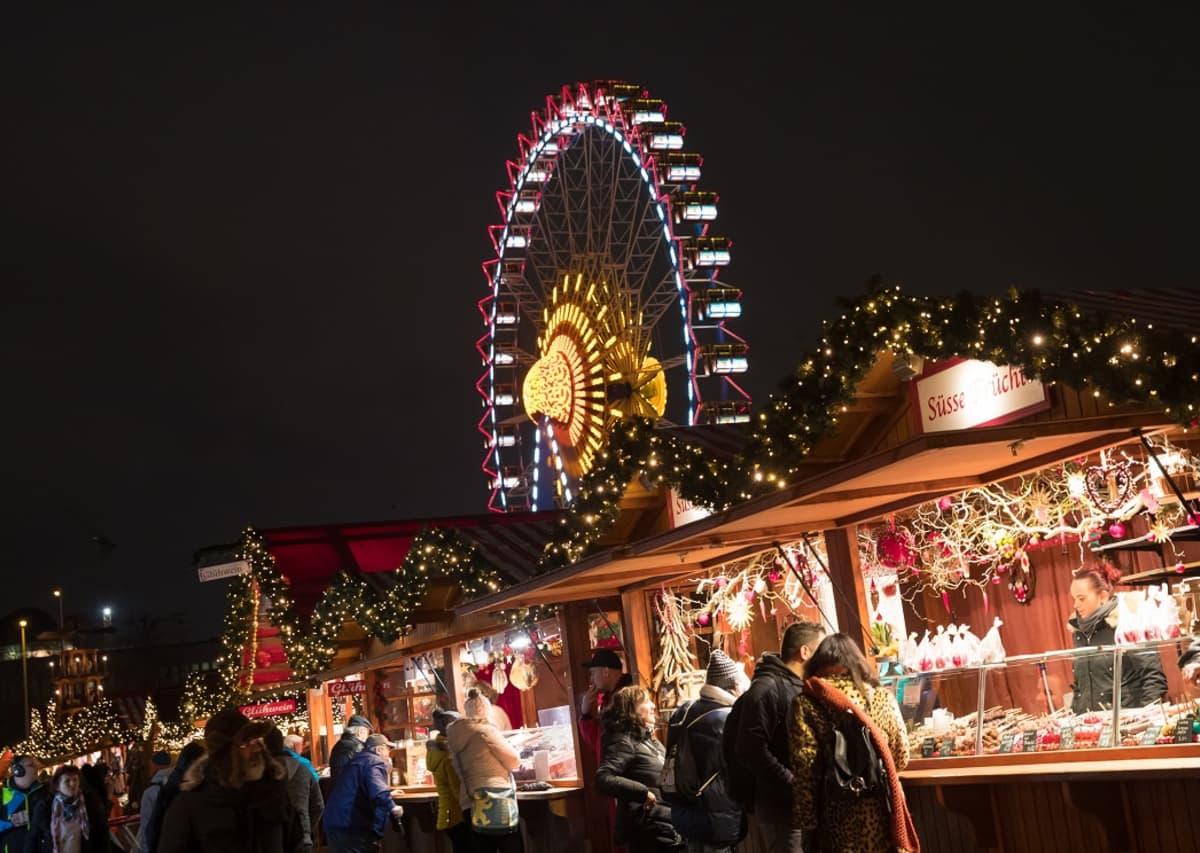 Valaistuja puisia myyntikojuja taustalla maailmanpyörä.