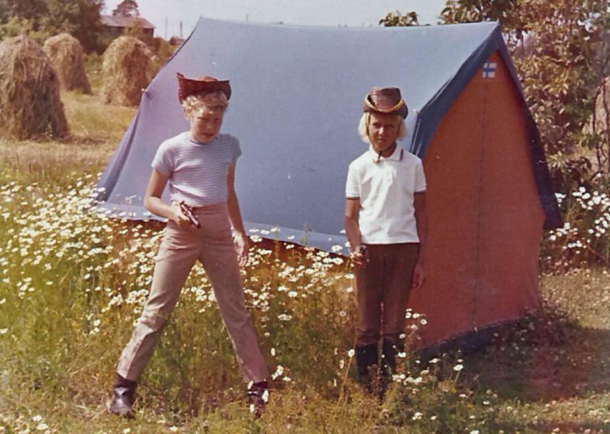 Kaksi poikaa teltan edessä leikkimässä cowboyta