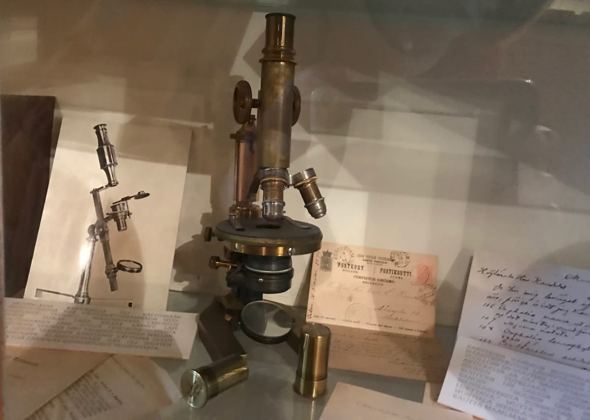 Vanha mikroskooppi lasivitriinissä.