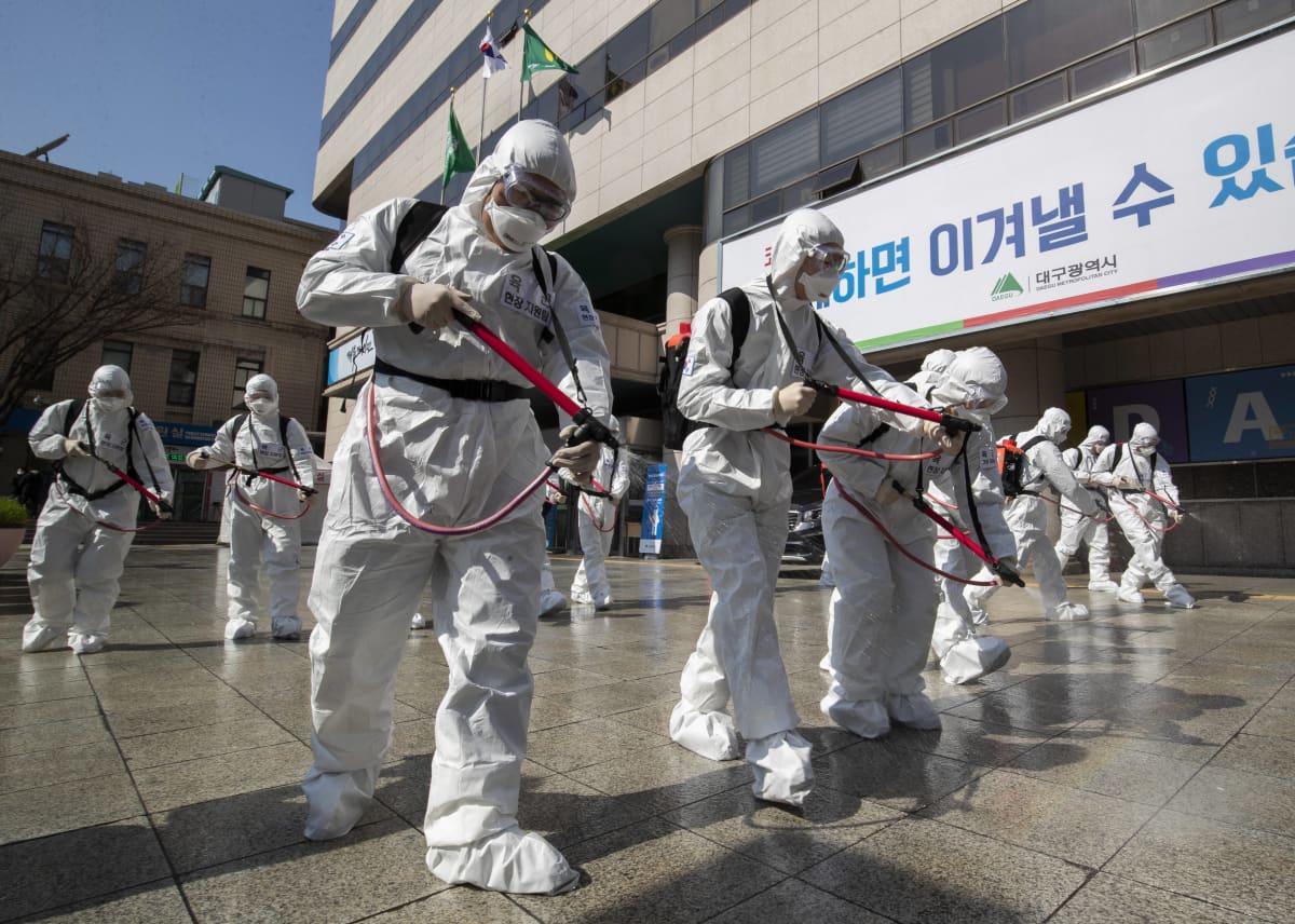 Suoja-asuihin pukeutuneet sotilaat suihkuttavat desinfiointinestettä kadulle Daegussa Etelä-Koreassa 2. maaliskuuta 2020.