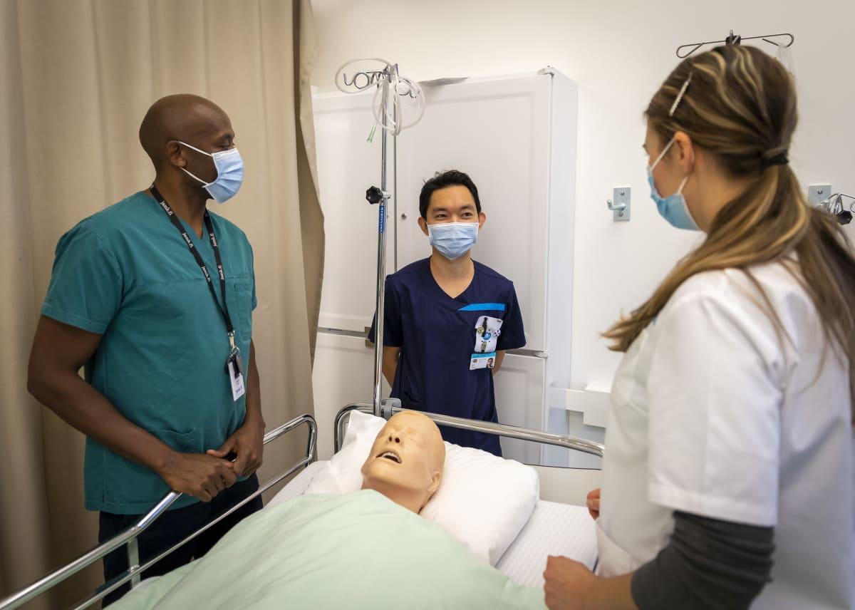 Suleiman Kamau, Floro Cubelo ja Marina Hirjaba juttelevat sairaalavuoteen ääressä.