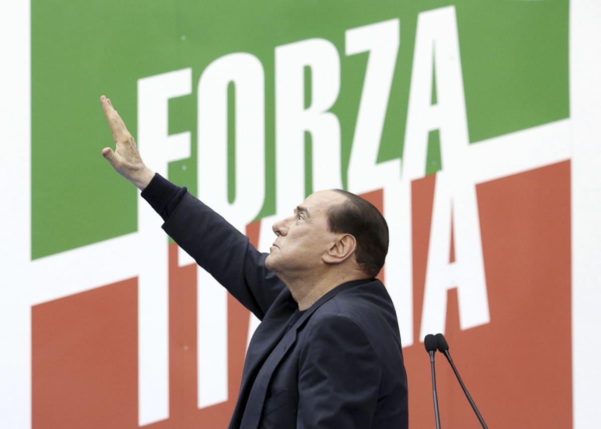 Silvio Berlusconi sivusta Forza Italia -kyltin edessä.