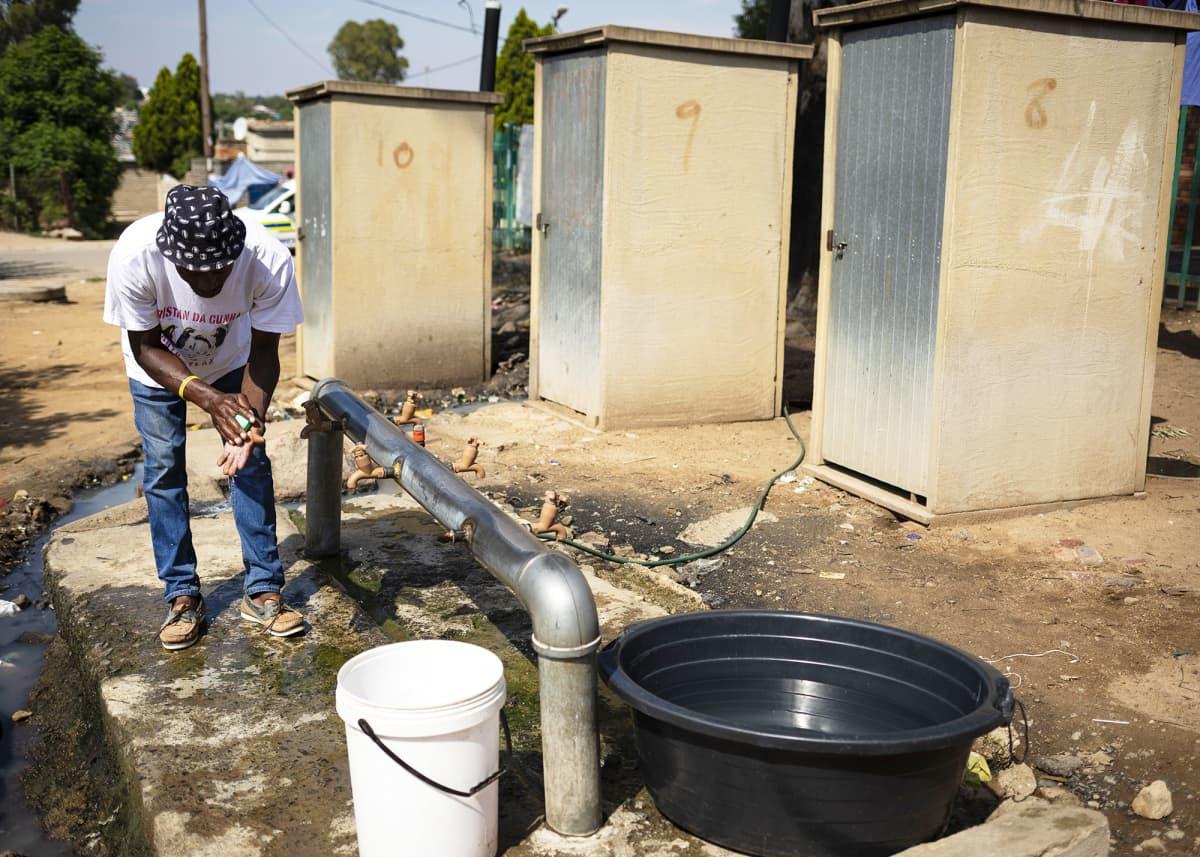 Asukas pesee käsiään kunnallisella vesipisteellä Johannesburgissa.