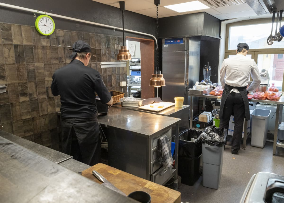 Kokki ja keittiömestari valmistavat lounasta ravintolan keittiössä