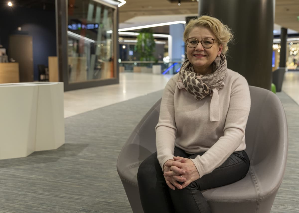 Anna Maria Heikkinen istuu tuolissa kauppakeskuksen aulassa.