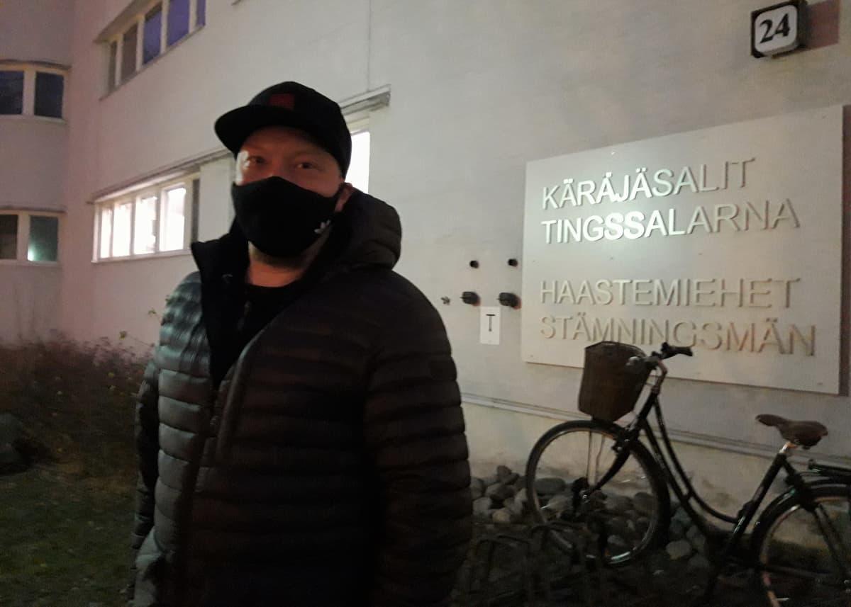 Mies seisoo käräjäoikeusrakennuksen edessä.