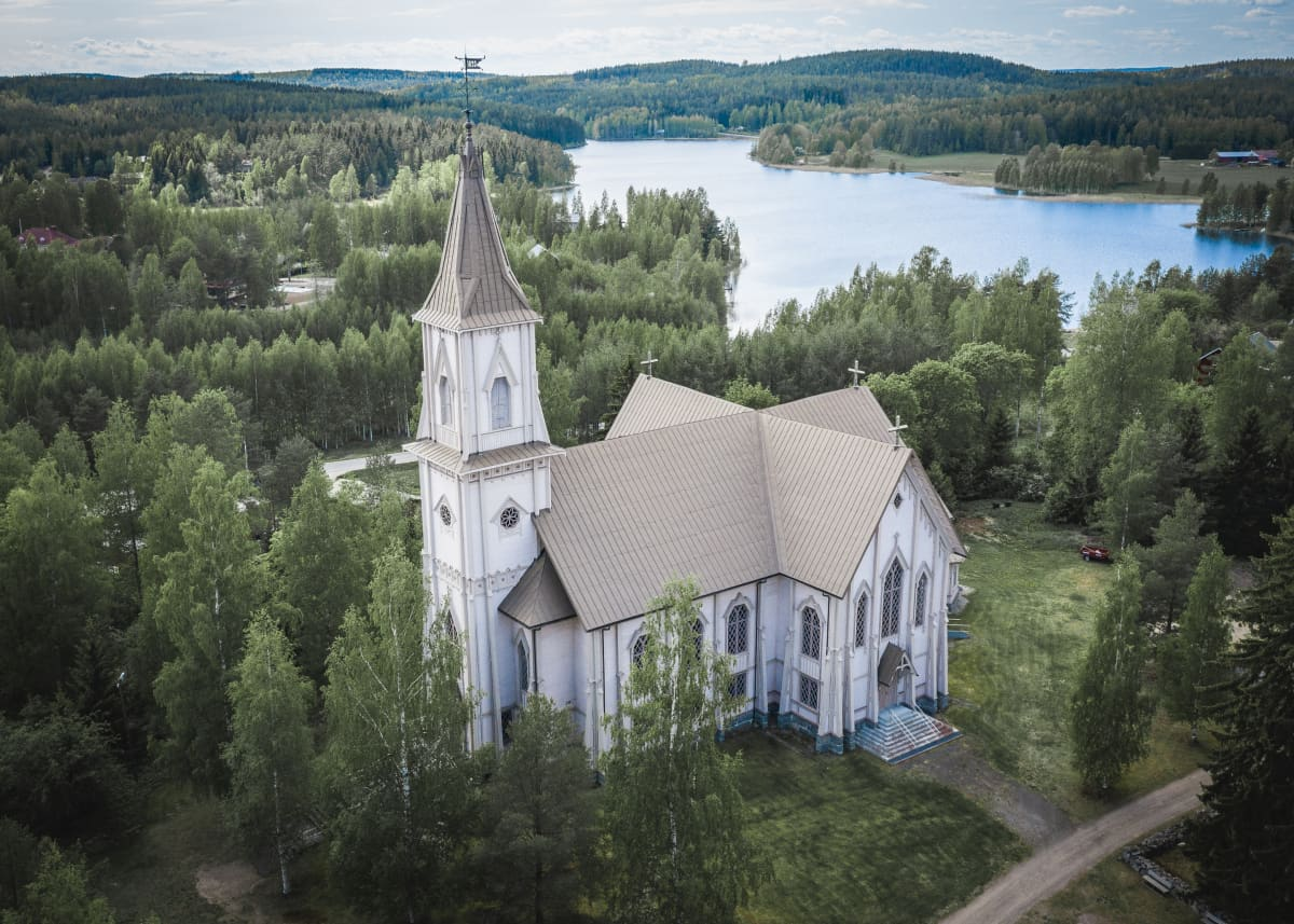Luhangan kirkko ja takana järvimaisemaa.