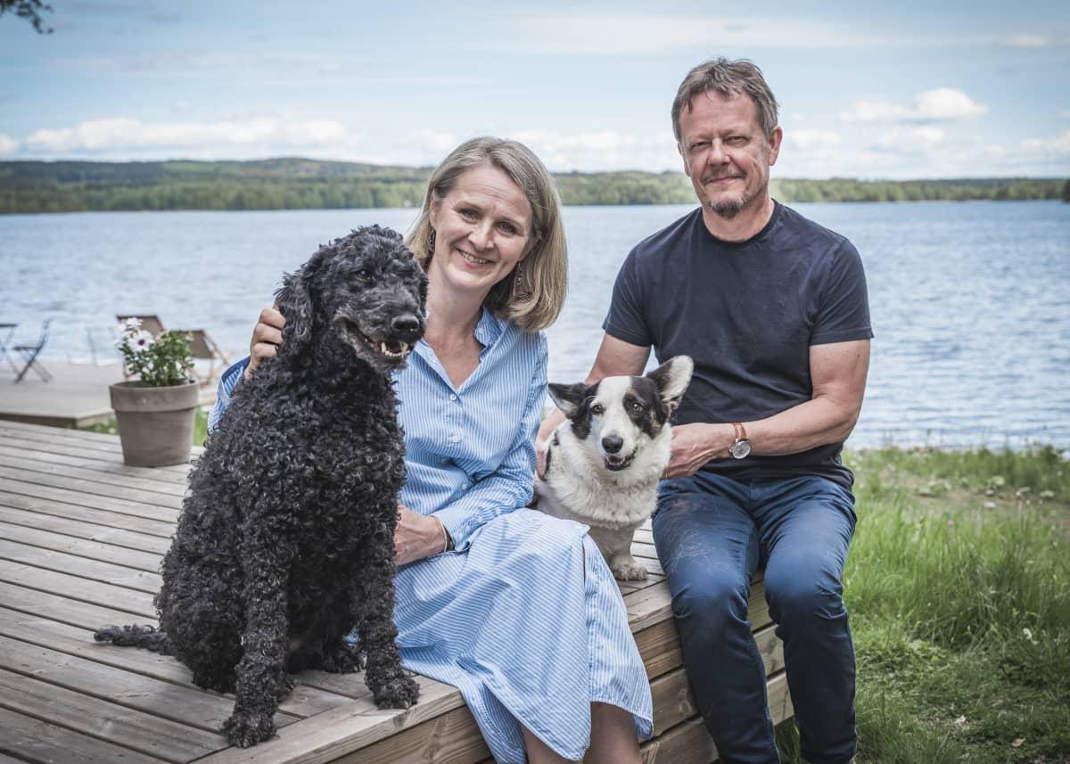 Kirsi Pohjola ja Kimmo Jokinen ja heidän koiransa järvenrannalla.