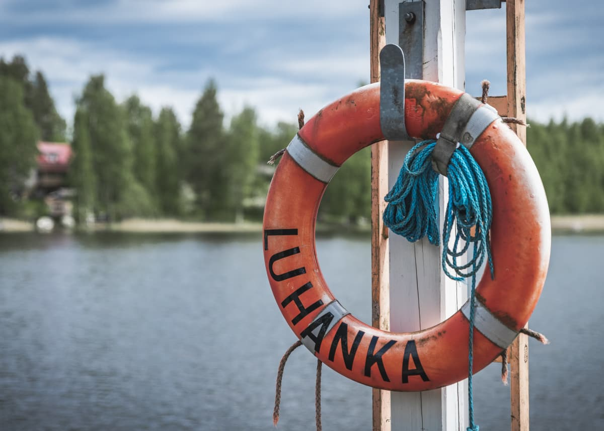 Pelastusrengas järven rannalla jossa luhanka teksti.