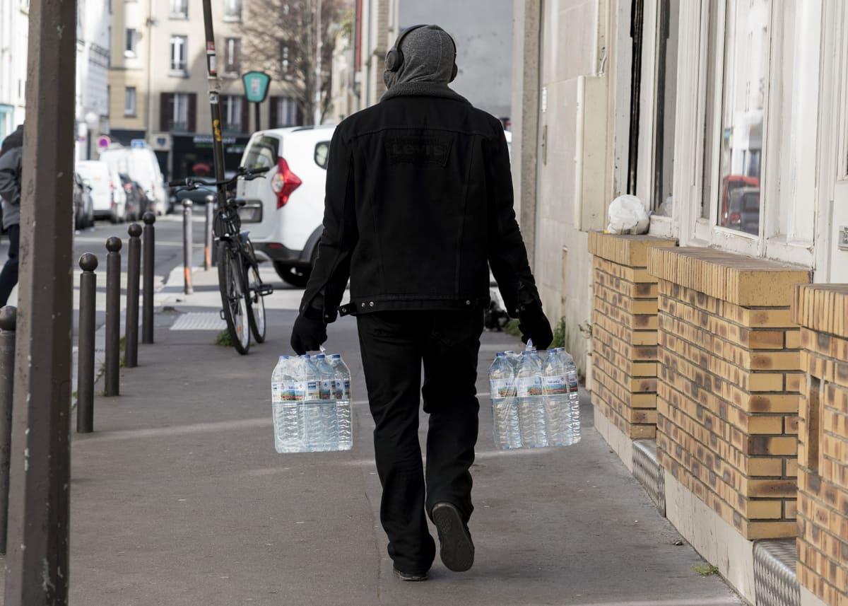 Mies kantaa vesipulloja kadulla.