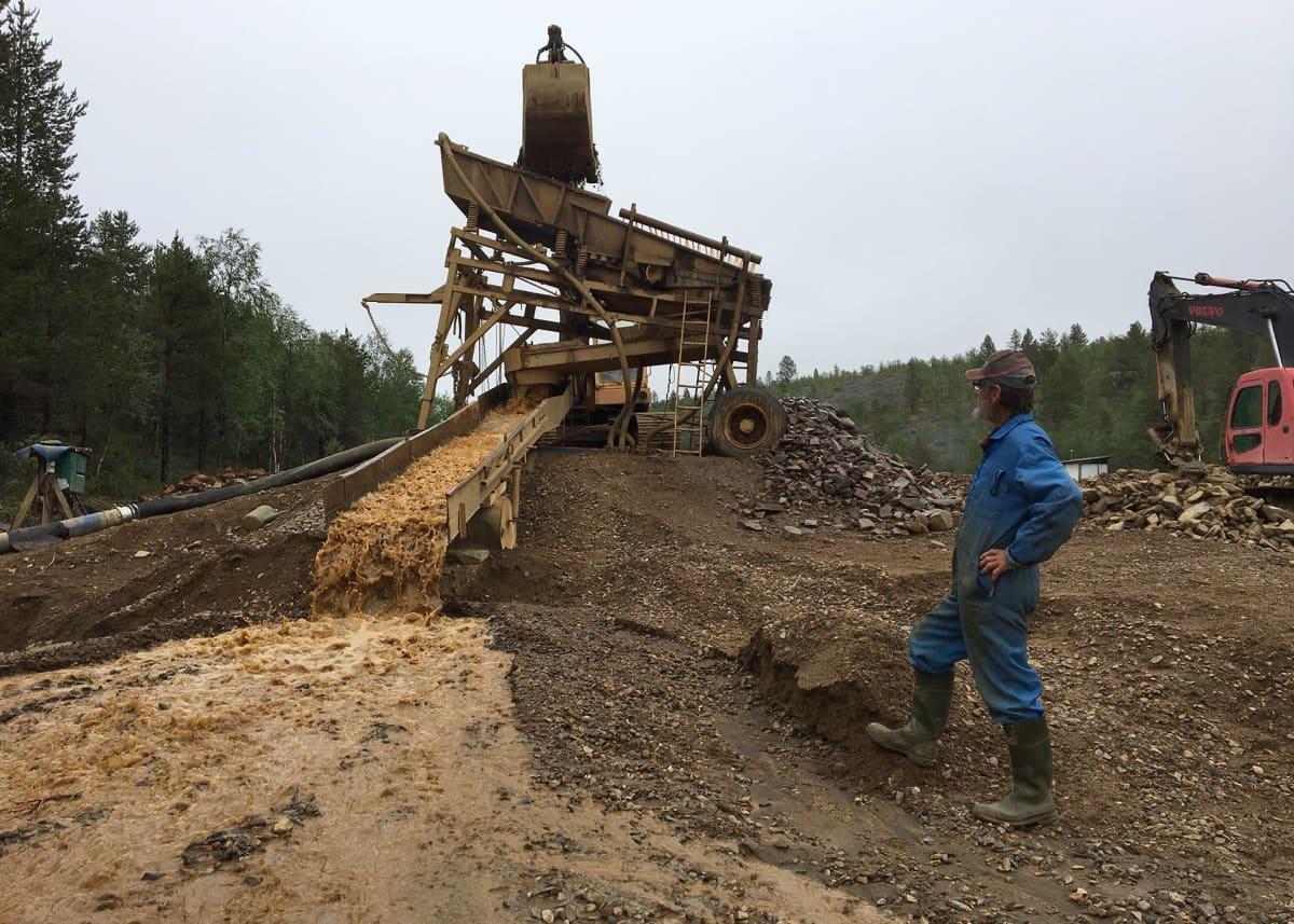 Raimo Kanamäki katsoo, kun kaivinkone nostaa soraa ränniin Lemmenjoella.
