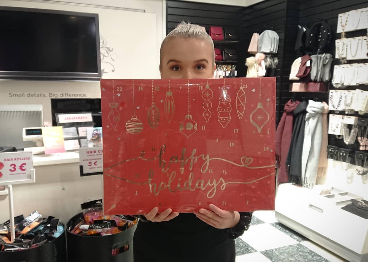 Heidi Malinen pitelee käsissään joulukalenteria Glitterin Joensuun myymälässä.