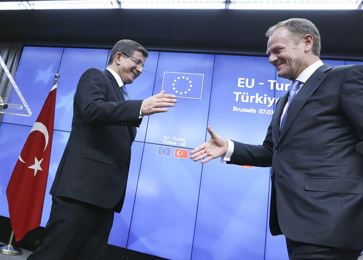 Turkin pääministeri Ahmet Davutoglu (vas.) ja Eurooppa-neuvoston puheenjohtaja Donald Tusk paiskaavat kättä.