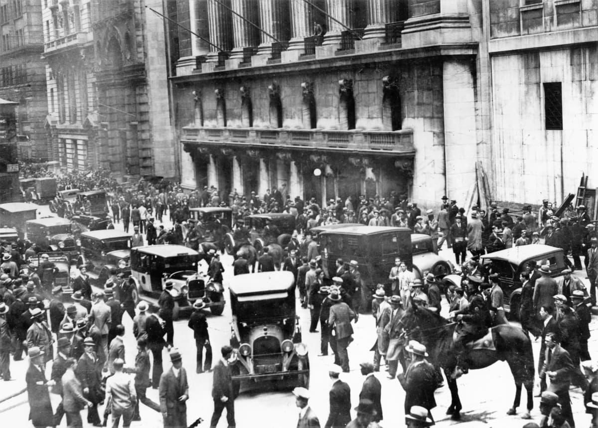 Kadulla parveilee ihmisiä jalkakäytävillä ja autojen seassa New Yorkin pörssin rakennuksen edustalla. Ratsupoliisi vahtii tilannetta kuvan oikeassa reunassa. Kuva on mustavalkoinen.