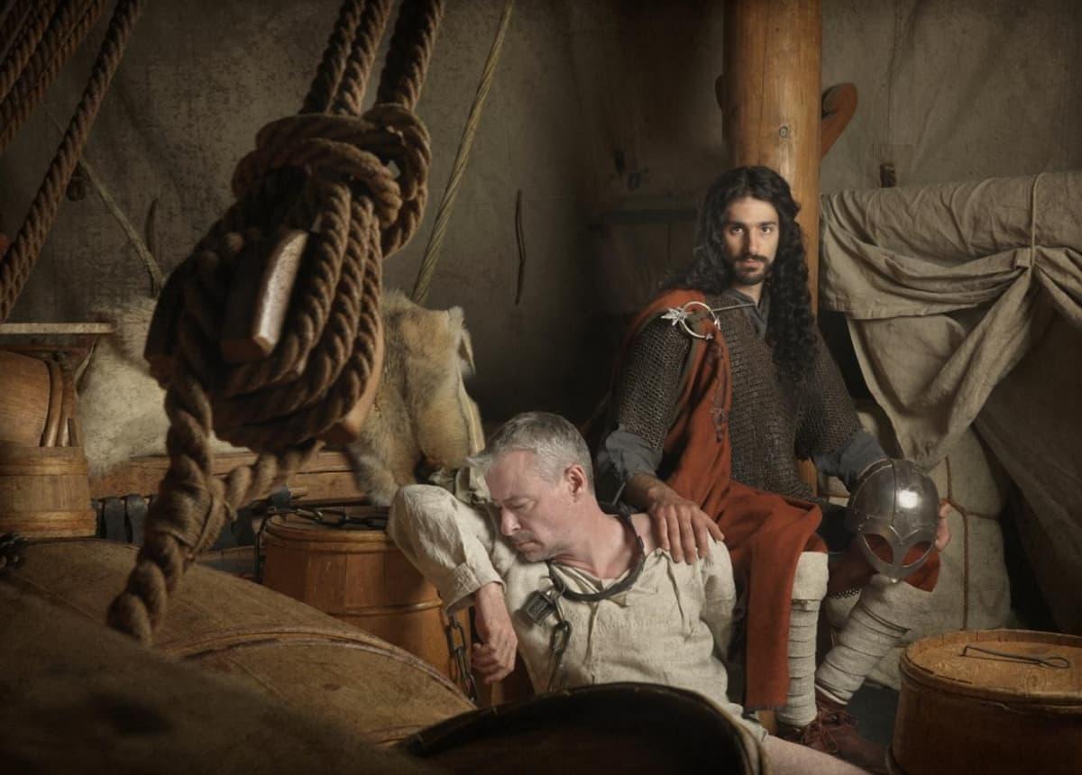 Kaksi miestä viikinkilaivan sisällä. Toinen on harmaantunut ja lyhyttukkainen, toisella on paksut, tummat kiharat.