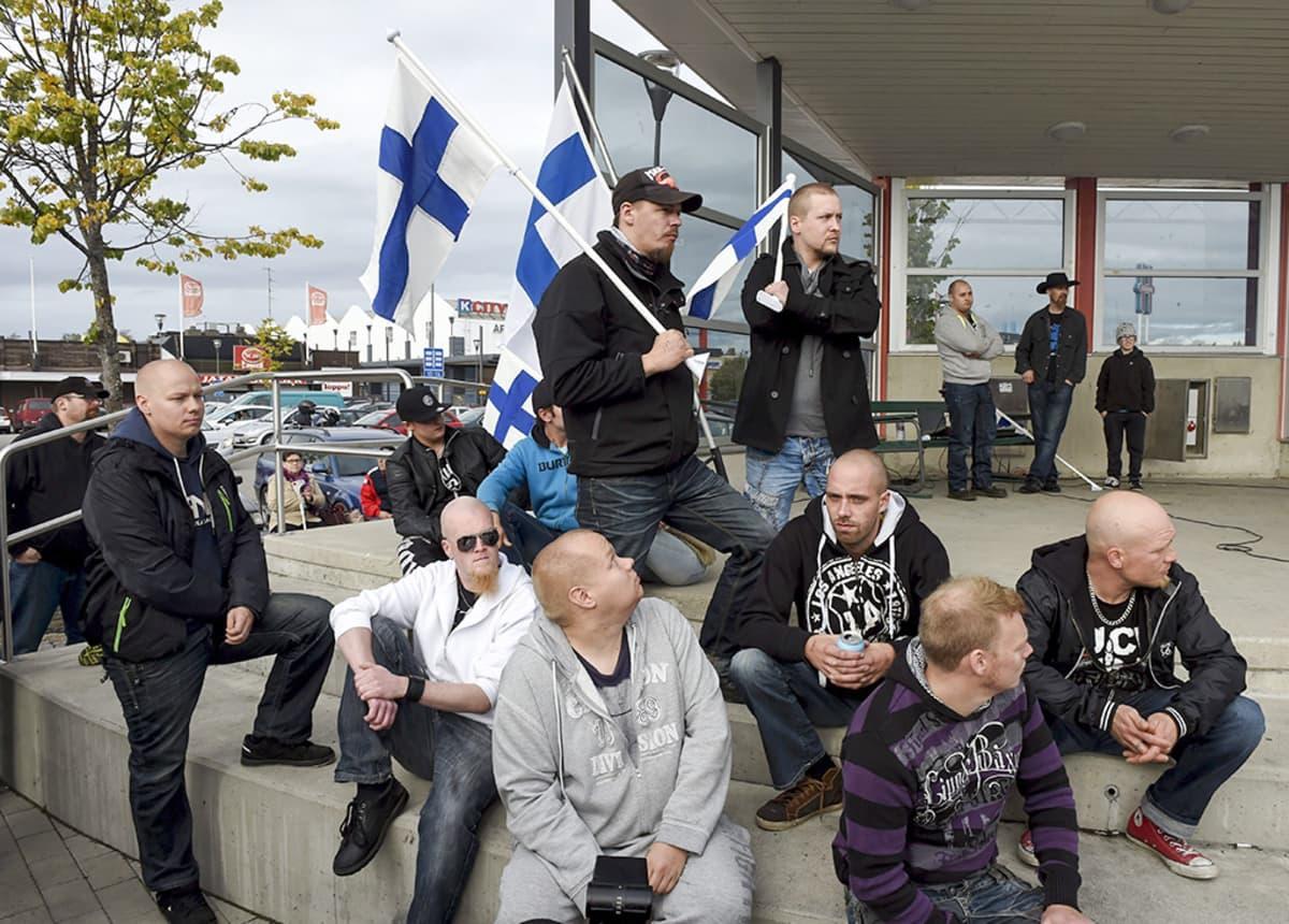 Miehiä joilla suomenlippuja käsissään