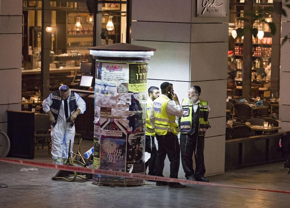 Pelastushenkilökunta partioi hyökkäyksen kohteeksi joutuneen ravintolan edustalla huomioliiveissä.