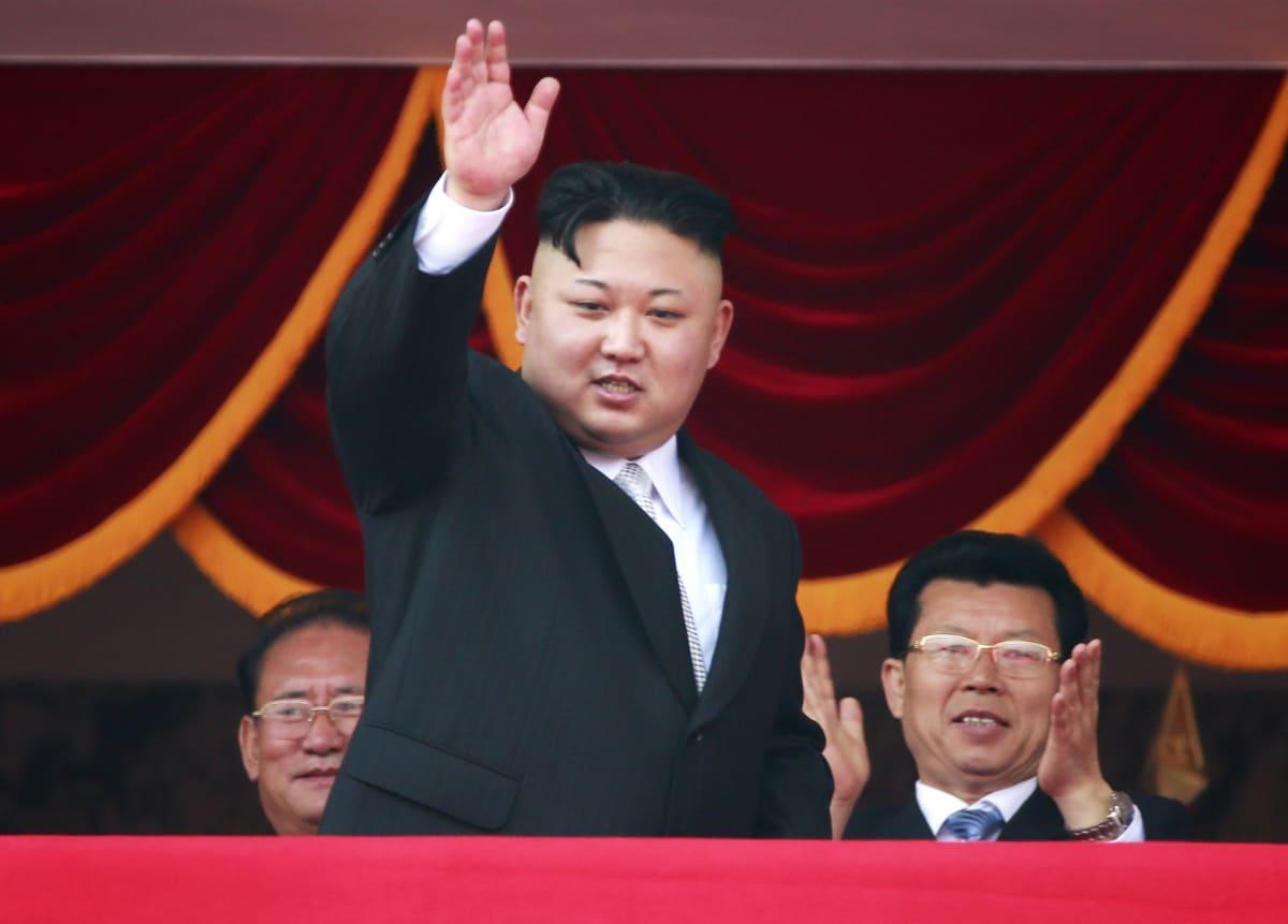 Kim Jong-un vilkuttaa. Taustalla istuu kaksi ihmistä.