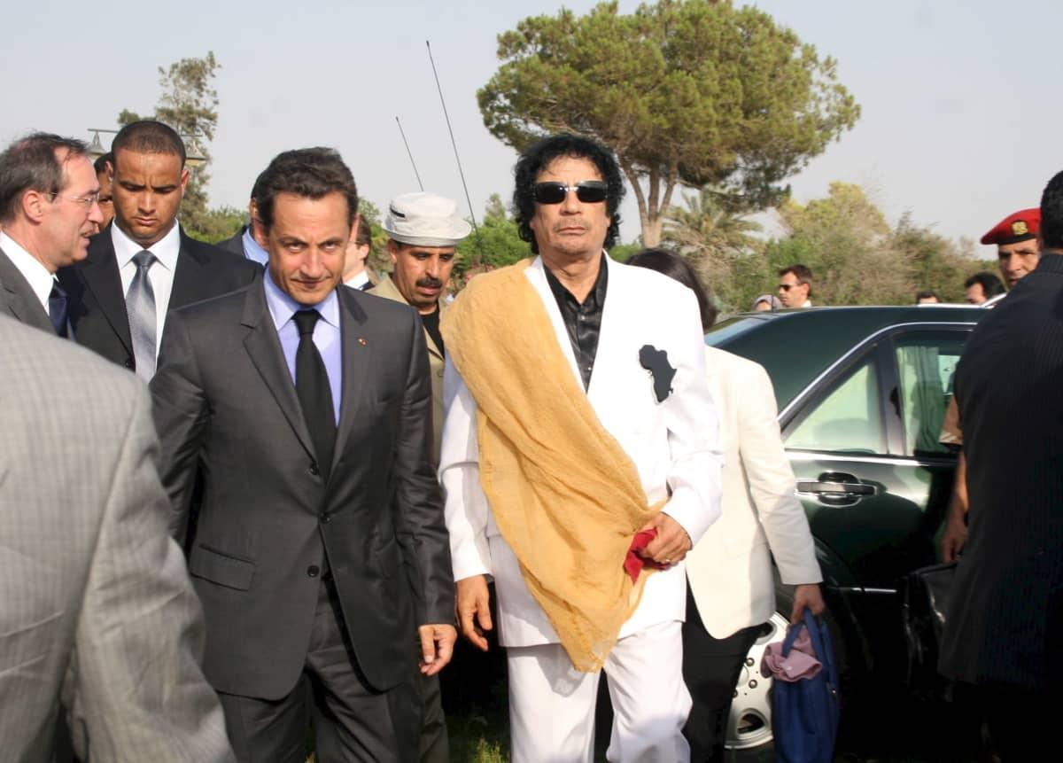 Sarkozy ja Gaddafi väkijoukon keskellä auton edessä