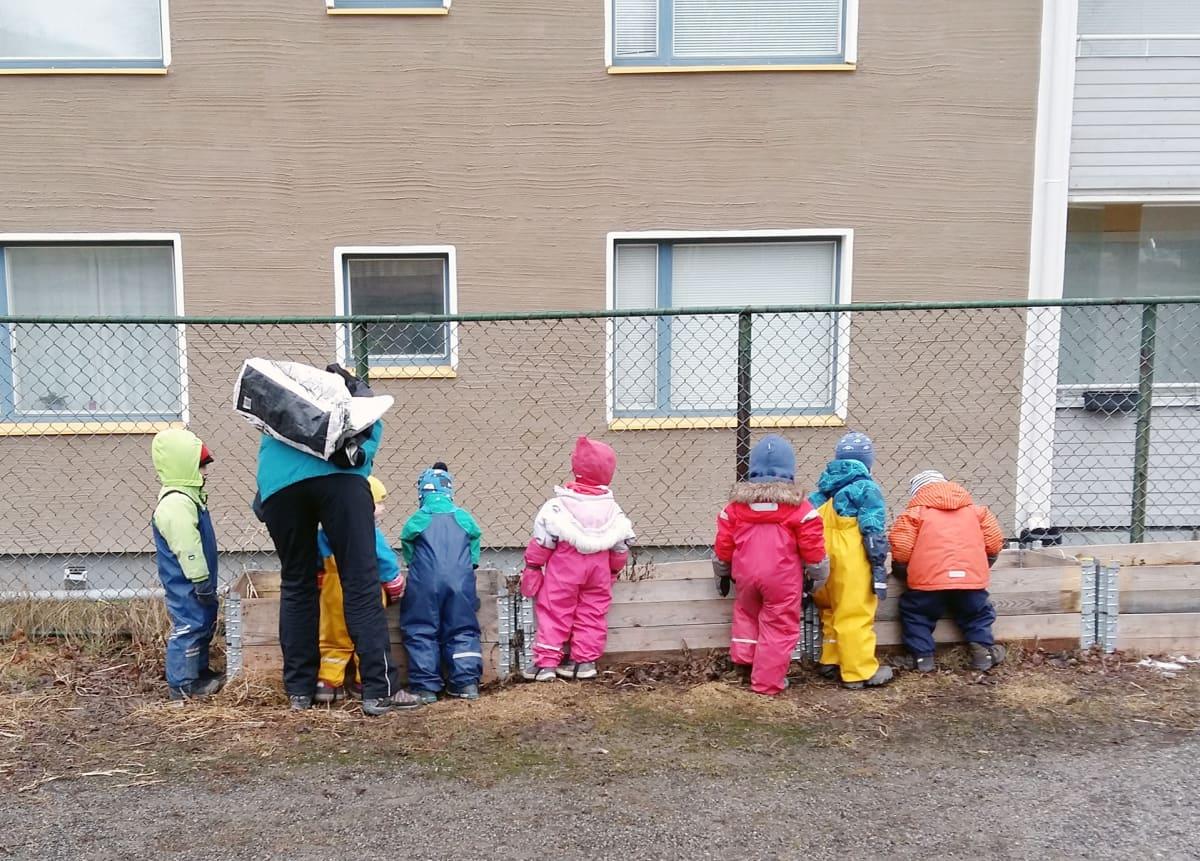 Kurahousuisia lapsia ulkona.