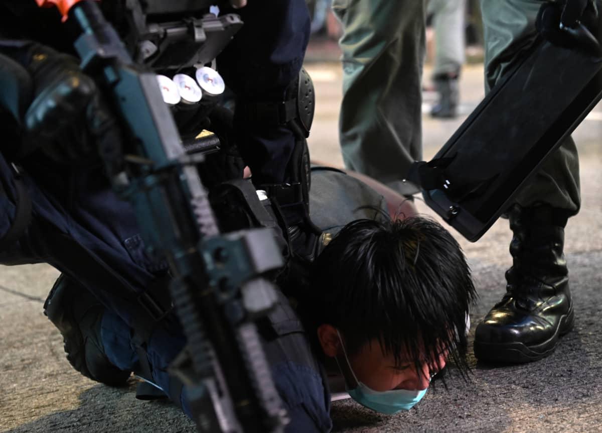 Poliisi taltuttamassa mielenosoittajaa Hongkongissa heinäkuussa. Hongkongilaiset aktivistit