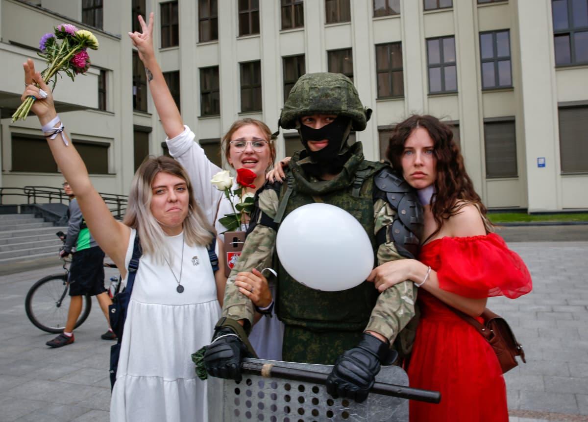 Naiset halasivat hallintorakennuksen edessä seissyttä sotilasta Minskissä.