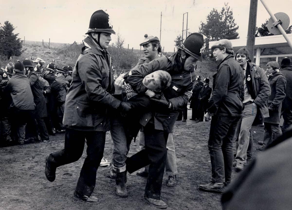 Poliisit kantavat miestä.
