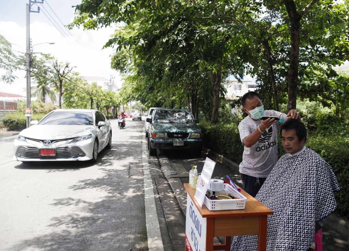 Thaimaalainen timanttikauppias menetti koronaepidemian vuoksi työnsä. Hän työskentelee nyt tienvarsiparturina Bangkokissa.