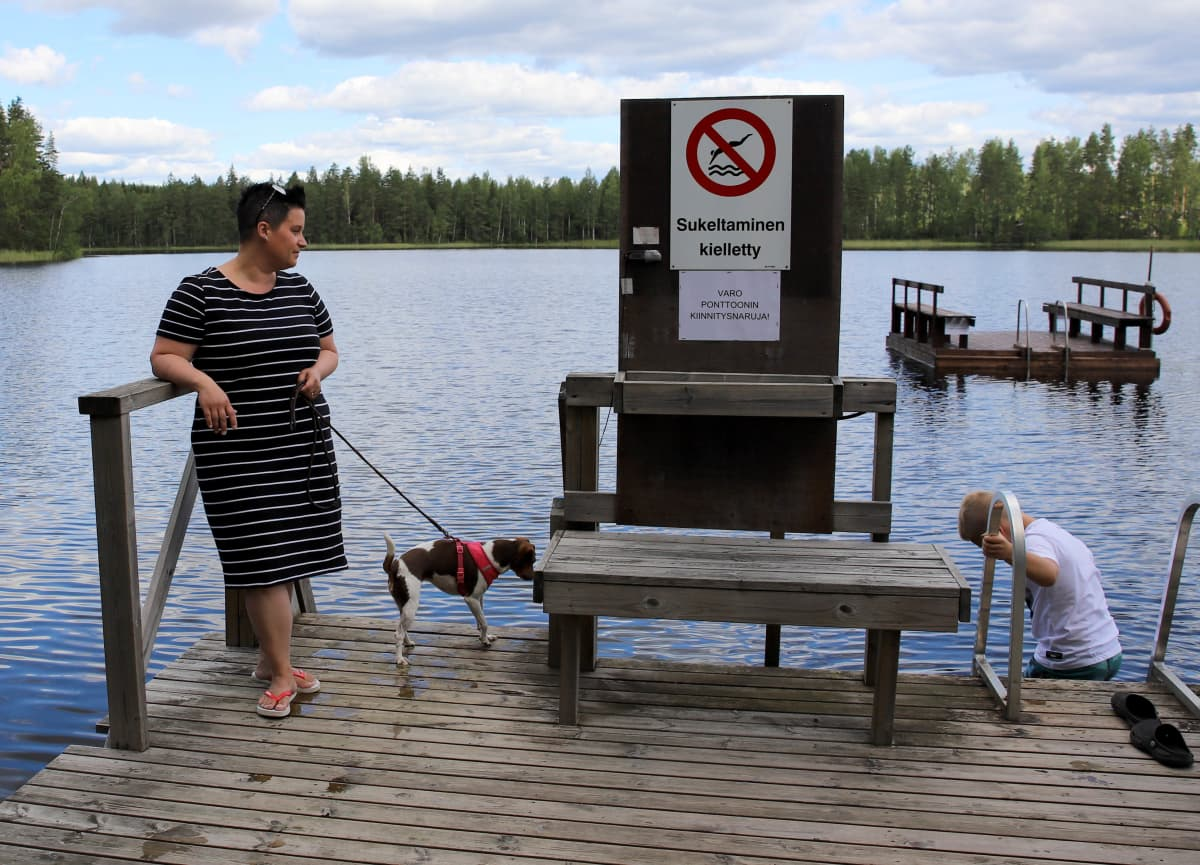Susanna Lahtinen koiransa Elsan ja poikansa Alexin kanssa Valkiajärven rannalla Purhon leirintäalueella.