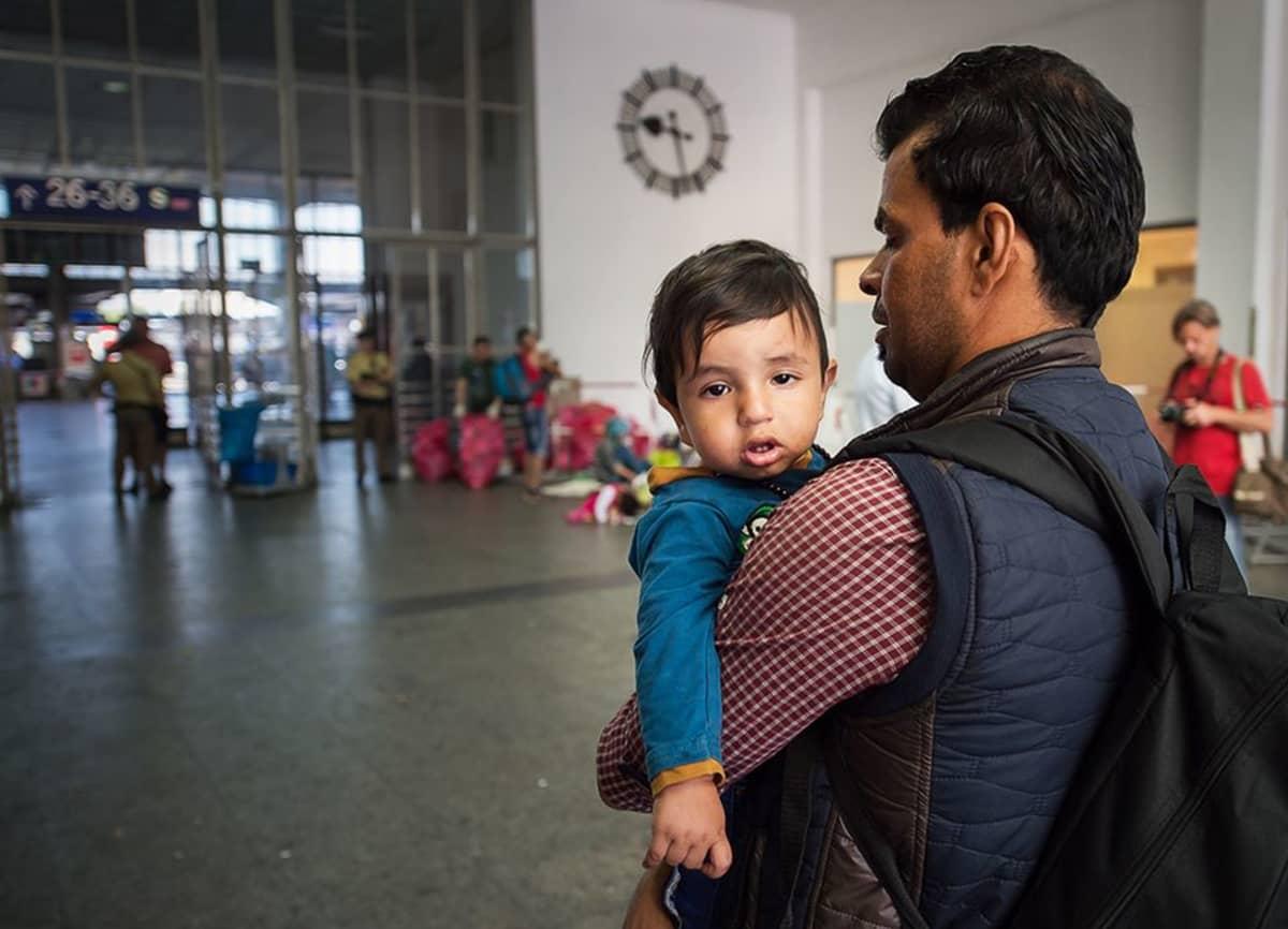 Pakolaismies pieni tyttö sylissään.