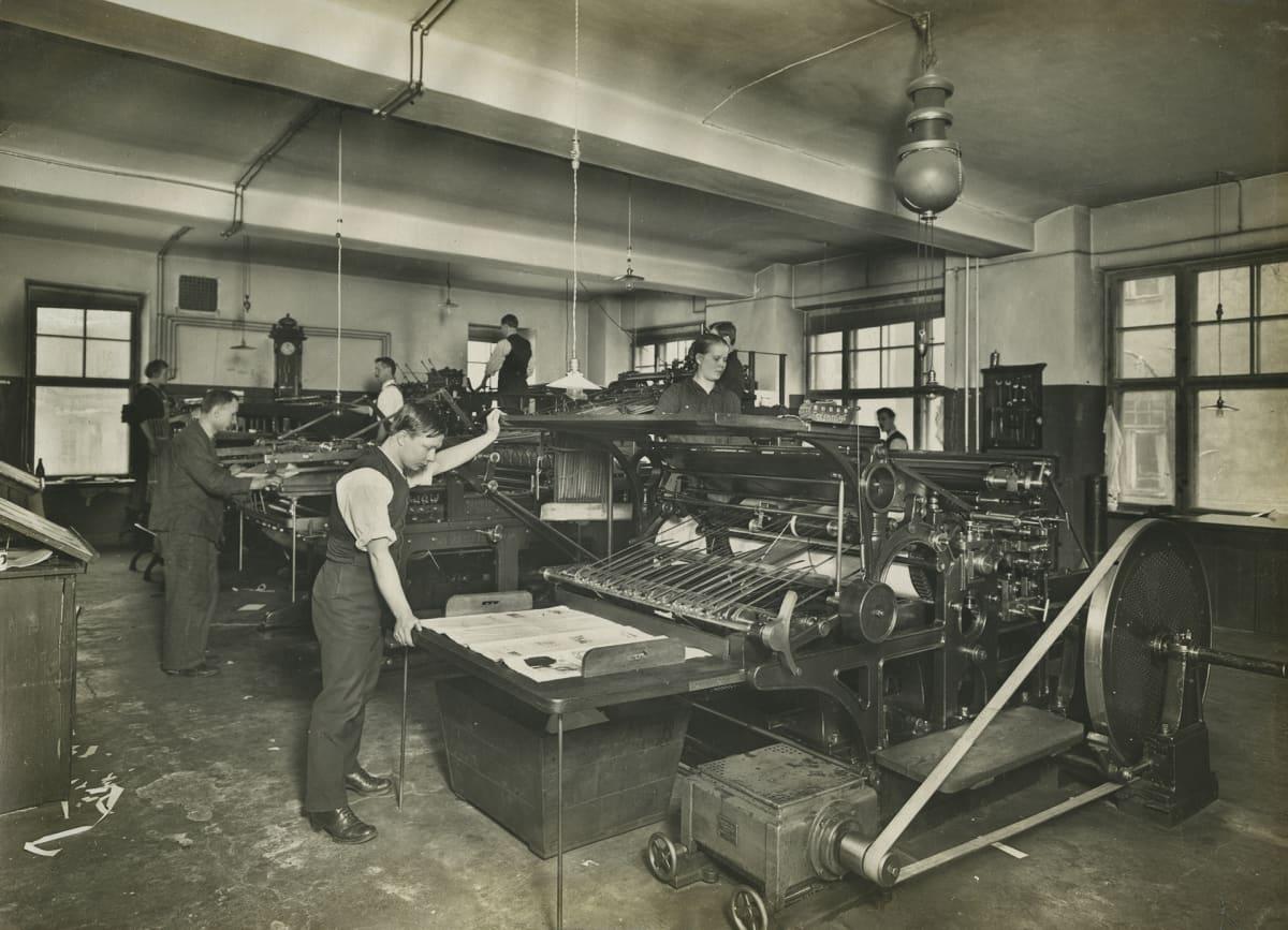 Työmies-lehden painaminen. Miehiä ja naisia työssään painokoneiden ääressä.