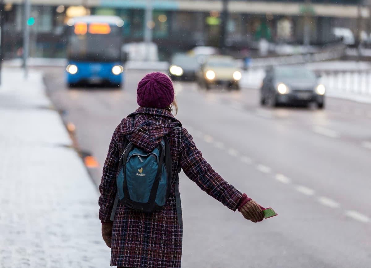 Matkustaja näyttää pysähtymismerkkiä bussille.