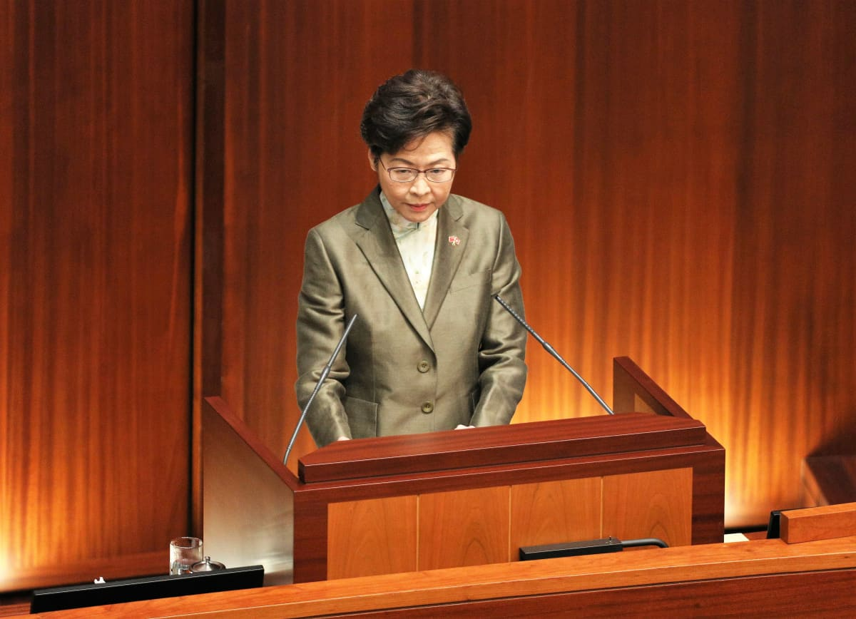Carrie Lam puhuu mikrofoneihin puhujanpöntön takana. Hänellä on tummanharmaa puku.