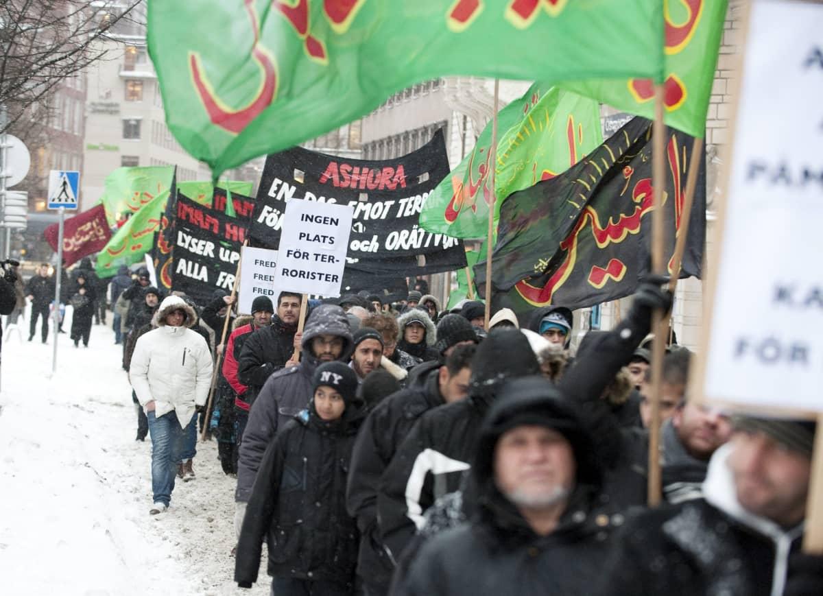 Mielenosoittajat kantavat kylttejä, joissa tuomitaan terrorismi.