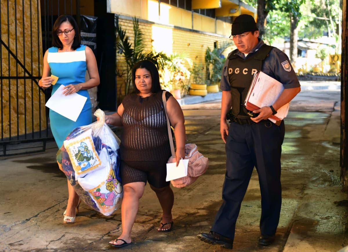 Nainen kävelee ulos vankilasta kantaen suurta läpinäkyvää muovikassia. Oikealla puolella miespuolinen vartija univormussa.